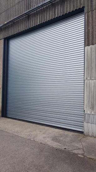 Installation d'un rideau métallique grand vent de grande taille sur Cambrai vue de l'extérieur.